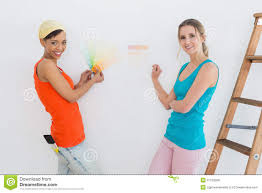 happy friends with ladder choosing color for painting a room