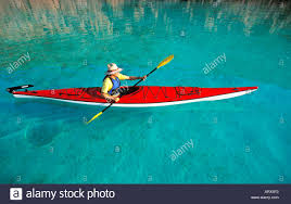 mexico baja sea cortes man paddling in red kayak through clear