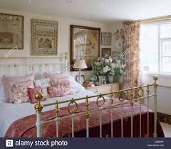 Pink Bedroom Cushions - antique samplers on wall above antique brass bed with pink quilt