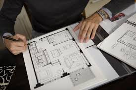an introduction to architecture a person adjusting floor plans in spiral bound sketch notebooks