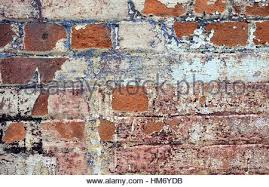 exposed brick cracked paint and peeling wallpaper around old