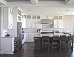 coastal white kitchen with dark grey island cabinets stacked