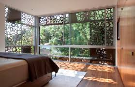 walnut residence with glass wall opens to the backyard
