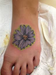 purple ink daisy flower tattoo on left foot