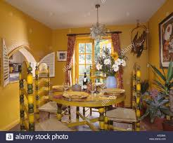 painted yellow chairs and table in bright yellow dining room with