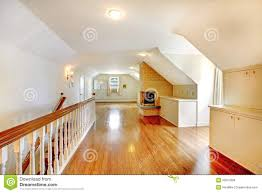 large long attic room with fireplace empty with golden hardwood
