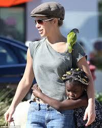 jillian michaels walks around with green parrot on her shoulder in