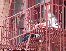 kirstie alley lights up a cigarette as she perches on the fire
