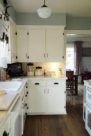 small kitchen and living spaces with white painted wood wall interior