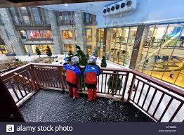 two children standing on a balcony looking down at snow in the
