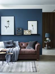 chic seating area with a brown sofa and a navy accent wall and textiles