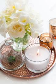 bouquet of white flowers in a vase candles on a copper tray