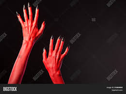 halloween red background red devil hands with black nails halloween theme studio shot on