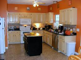 orange wall color plus cream wooden kitchen cabinet with black