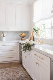 marble countertops white cabinets and brass fixtures exactly what