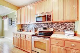 oak kitchen cabinets with stainless steel appliances light wood cabinets with multicolored backsplash and modern stainless