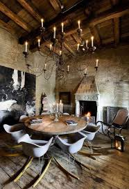 rustic dining room with large wrought iron chandelier over round