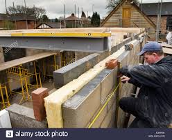 house builder self building house builder checking level of exterior wall with