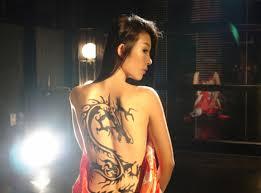 big black dragon tattoo on the back of a woman