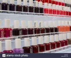 rows of essie brand nail polish bottles store interior nyc stock