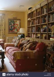 Red Sofa In Living Room by Red Sofa Piled With Cushions In Front Of Large Fitted Bookcase In