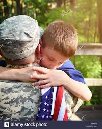 A American Flag Pictures A Soldier Father Is Hugging His Son Holding An American Flag