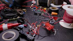 male hand searches a cluttered black table of electrical wire