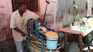 editorial vendor extracting juice from sugarcane with a hand