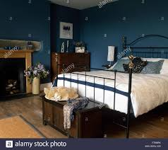black wrought iron bed with white duvet in a blue bedroom with a