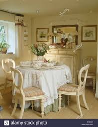 cottage dining room furniture cream chairs with checked upholstered seats at circular table with