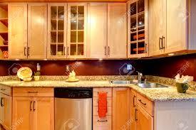 light tones kitchen storage combination with burgundy backsplash