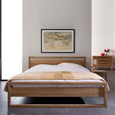 bed on the floor brown teak bed frame with brown blanket on the floor connected by