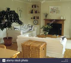 large basket behind white sofa in cream living room with tall tree