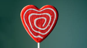 heart shaped candy heart shaped candy lollipop with and white swirls against a