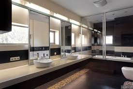 his and hers twin sinks in modern mirrored bathroom with large tub