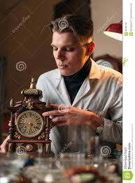 watchmaker with old mechanical desk clock stock photo image