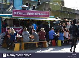 people sitting on benches eating outside a mexican restaurant on