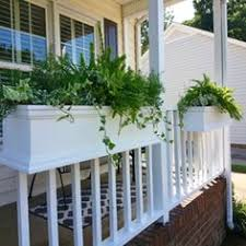 rail planters and hanging baskets on white porch window boxes