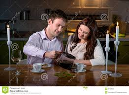 Romantic Dinner At Home by Young Couple Having Romantic Dinner On The Dinner Table At Home
