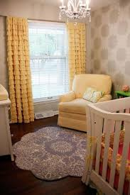 baby room with yellow ruffle curtains and hardwood floors the