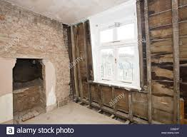 brick wall stud wall and fireplace in room undergoing renovation