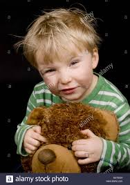 teddy boy hairstyle smiling little boy with brown teddy bear on black background boy
