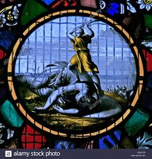 a stained glass window depicting david slaying goliath flemish