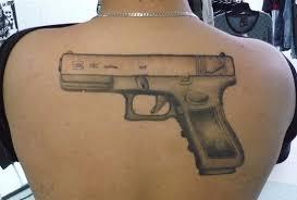 grey ink gun tattoo on upper back