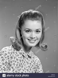 updated flip hairdo 1960s portrait smiling woman wearing print blouse with flip hairdo