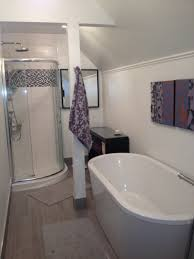 Small Bathrooms With Corner Showers Oval White Corner Bathtub Placed On The Brown Wooden Flooring Plus