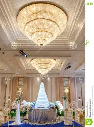 wedding cake and flowers decorations with chandelier on ceiling