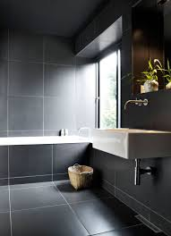 bathroom tile idea use large tiles on the floor and walls 18 the use of white grout around these large dark tiles works well because the grout doesn t take over the bathroom the tiles are large enough to use such