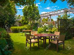 landscaped garden with wooden dining table set in the shade of