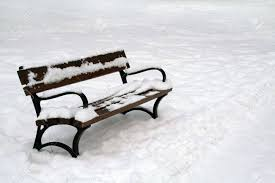 wooden bench in winter clear snow on ground and on bench stock